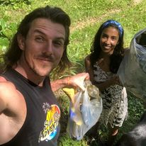 Tom Wright and Carolina Castañeda are holding bags of rubbish they cleaned in Bocas del Toro, Panama