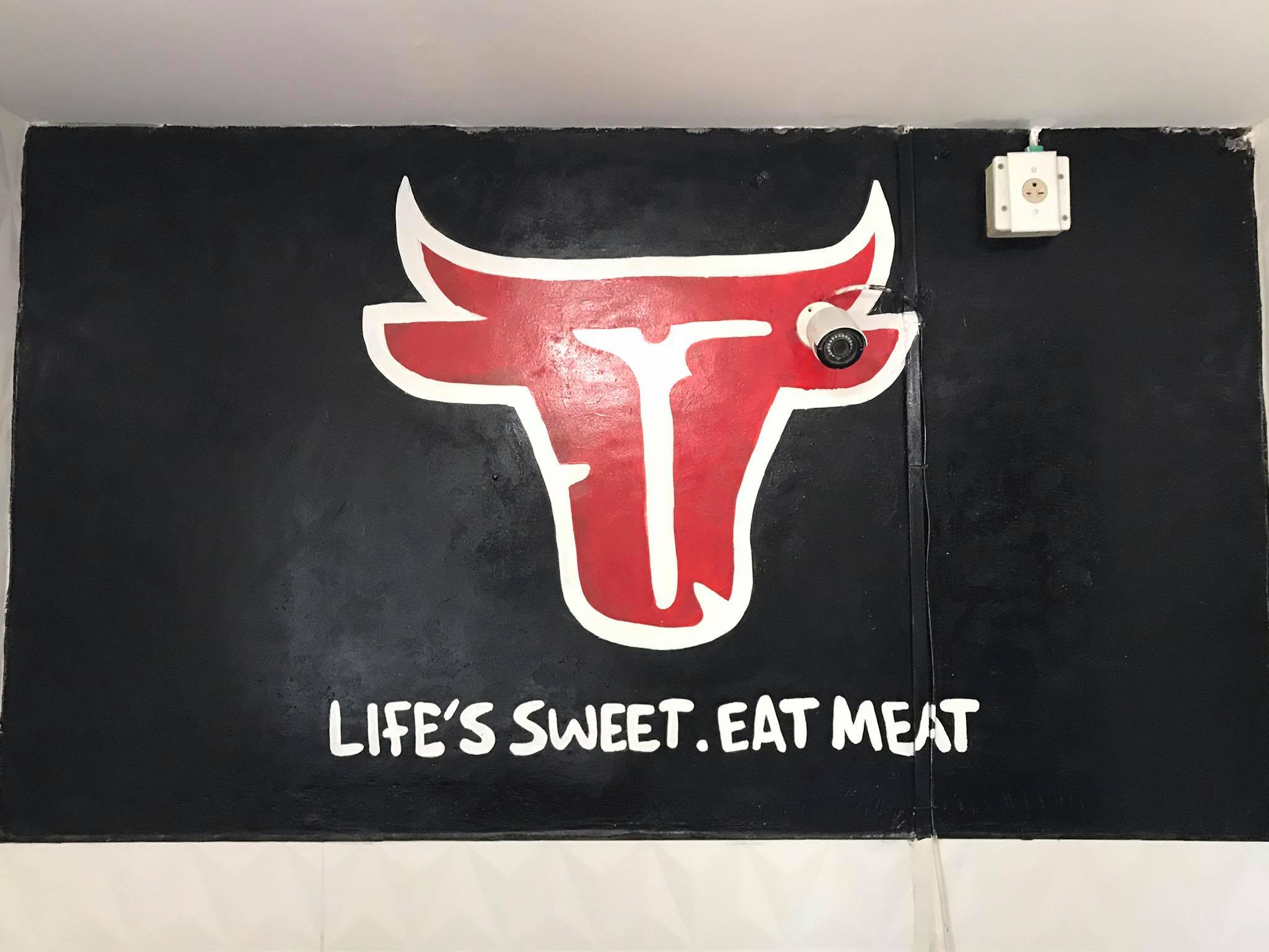 """A painting of a red steer skull silhouette, with a black background and white letters that read """"Life's Sweet. Eat Meat"""""""