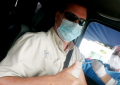 Mark Johnson is seated in a vehicle as a nurse on the outside of the car administers his first dose of the AstraZeneca vaccine into his arm through the window of the car at the baseball stadium in Changuinola el Estadio Calvin Byron.
