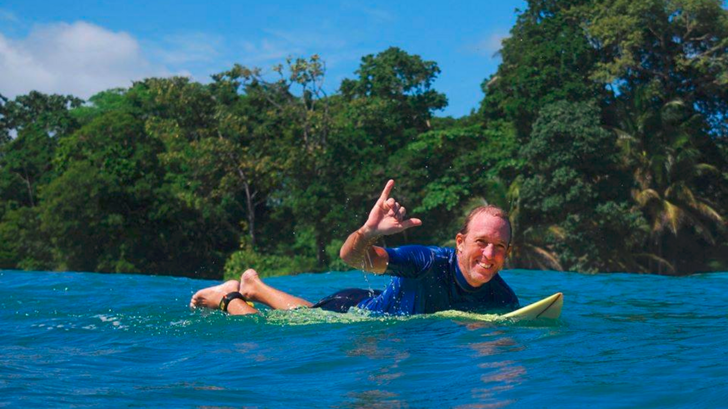Andy Crawford on a surfn board in the Caribbean Sea giving the shaka sign with his right hand and smiling