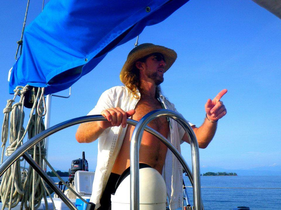 Captain Andy behind the wheel of his sailboat