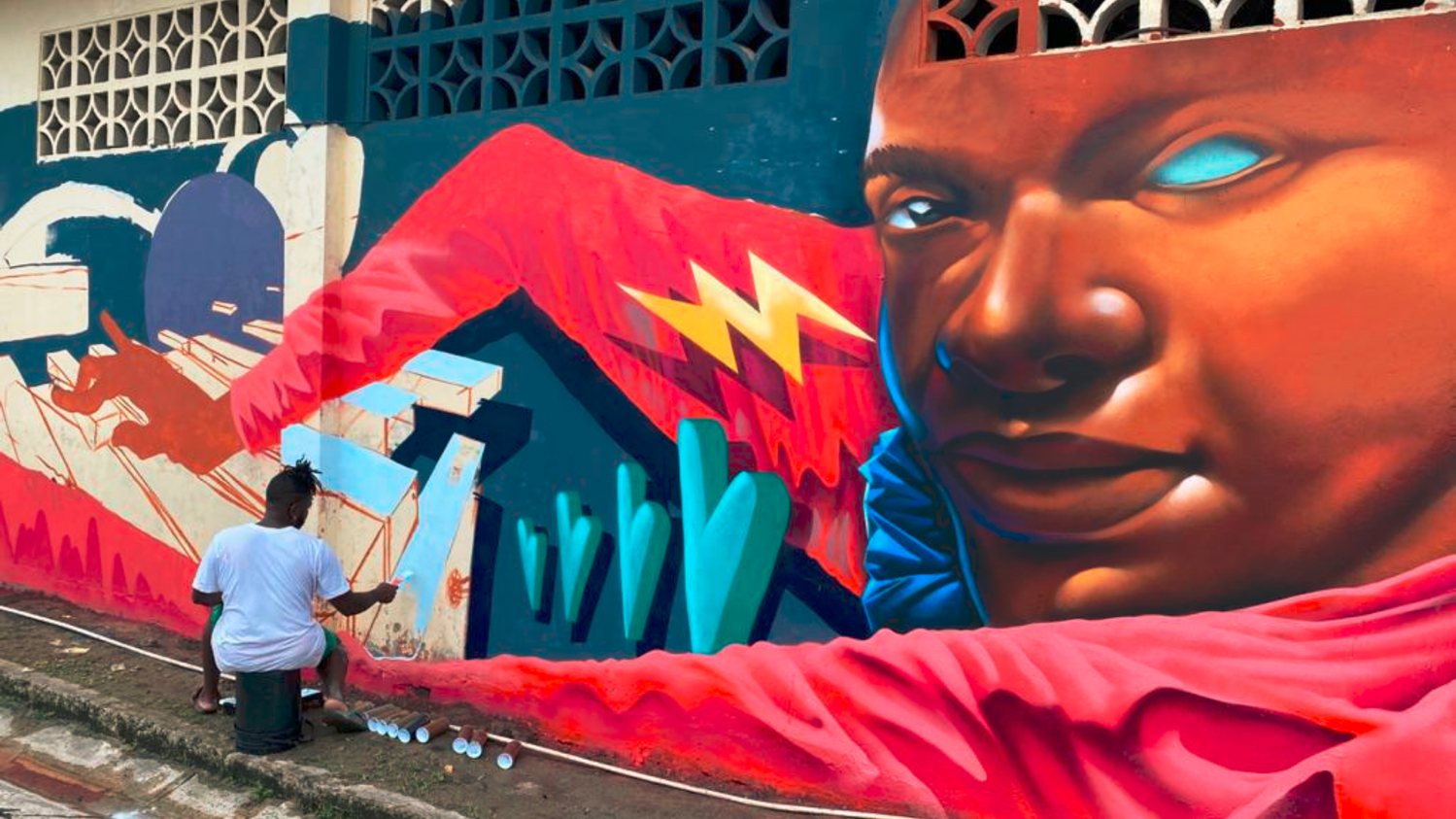 The artist Sergio Smith, also known as Madmagos, is painting a street mural dedicated to Luis Russell