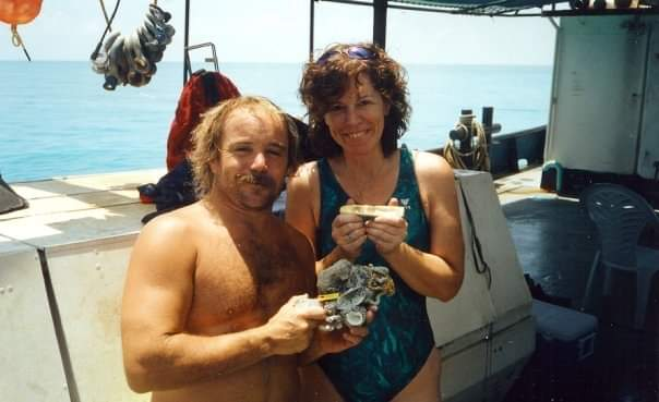 Jeff Dickinson and Deborah Cruze in Key West on a boat posing with gold found on the Mel Fisher expedition