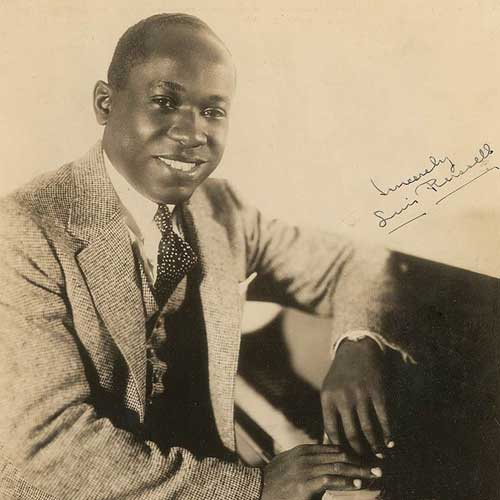 A black and white photo of Luis Russell seated at a piano.