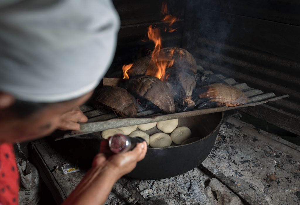 A lady cooking over fire