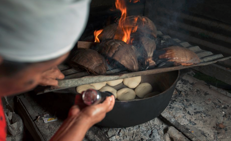 lady cooking coconut rolls over fire