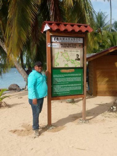 Gustavo Smith stands next to La Ruta de Tormena monument in Boca del Drago at Yarisnori