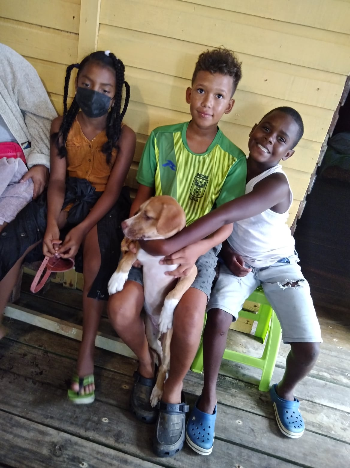 three children smiling with a dog