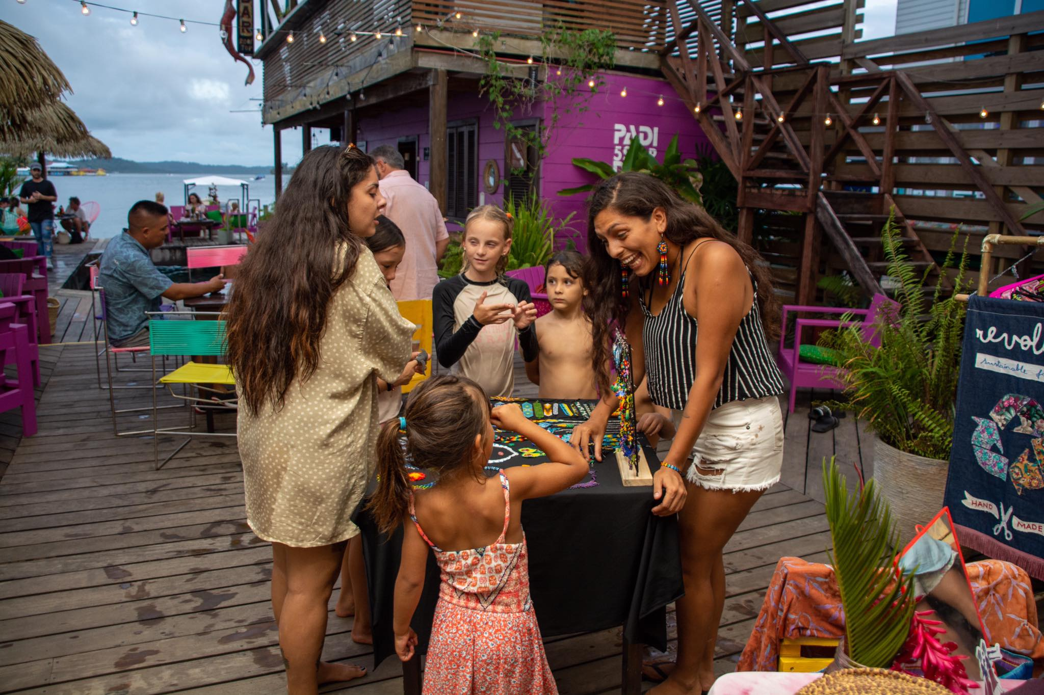 vendors and children smiling at jewelery at La Buguita Ocean Lounge during their friday market